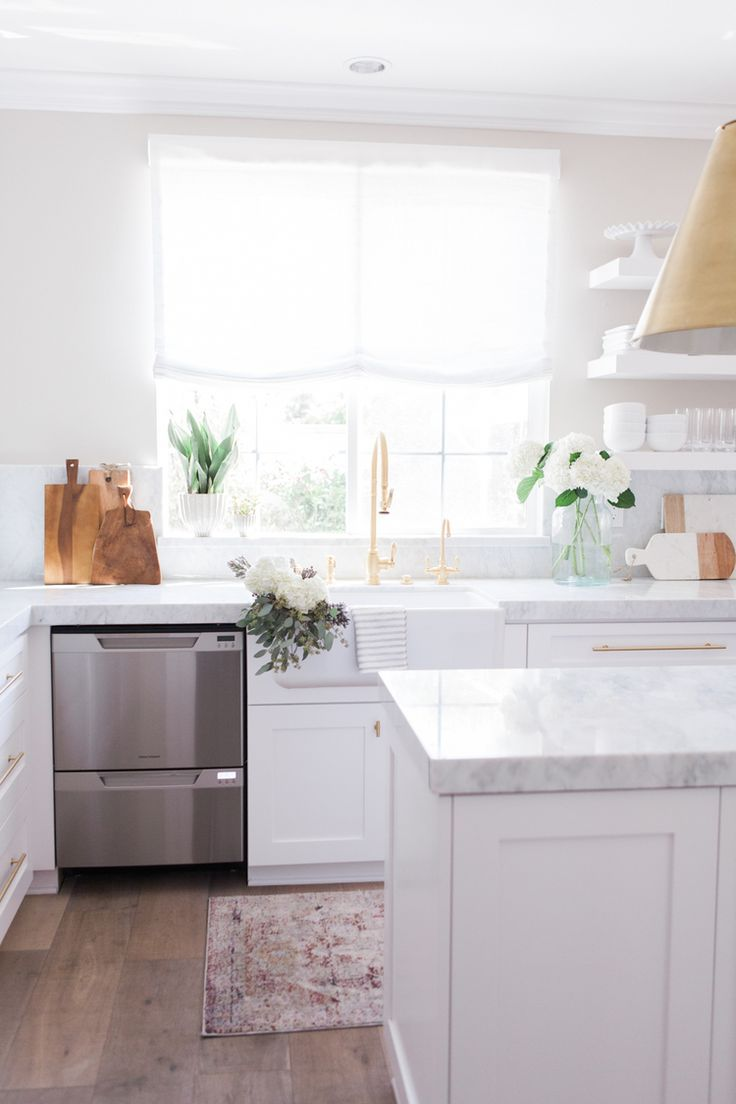 White cabinetry, light grey bench and brass fittings