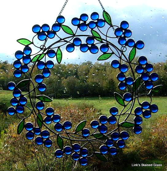 """Stained Glass Blue Berry Wreath. Blue glass nuggets with stained glass green leaves. Wire work and center heavy metal ring for extra strength. Chain included. Measures: 11""""."""