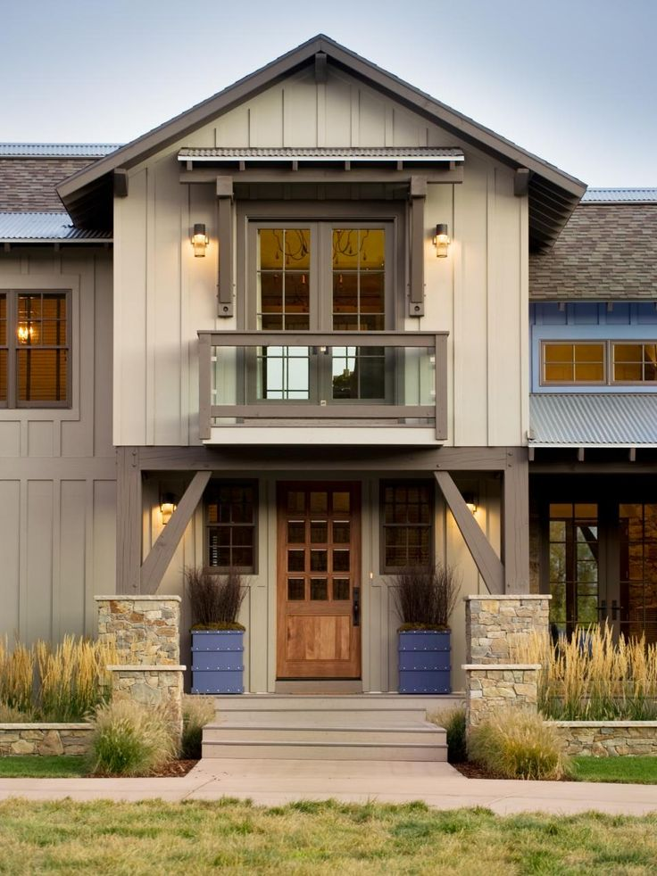The front entry of HGTV Dream Home 2012 in Park City, UT. features a timber-framed porch, stone pillars, blue planter boxes and a Juliet balcony overhead.
