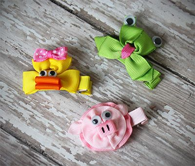 These folded ribbon animal clippie bows are as cute as can be. Each double pronged alligator clip is lined with ribbon and embellished with an adorable animal face crafted from grosgrain ribbon. These animals have sweet details like a pink bow (on the duck), a mischievous tongue sticking out on the little frog, and silly googly eyes on all the animals. We love the bow art on these animal hair clips!  Each clip is about 2