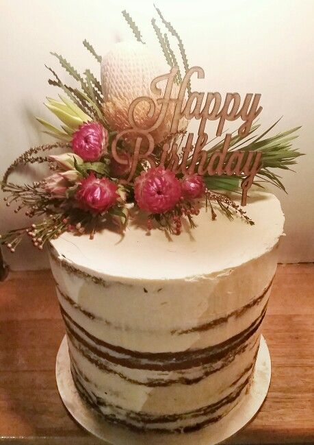 Semi naked cake decorated in a rustic style with Australian native flowers.