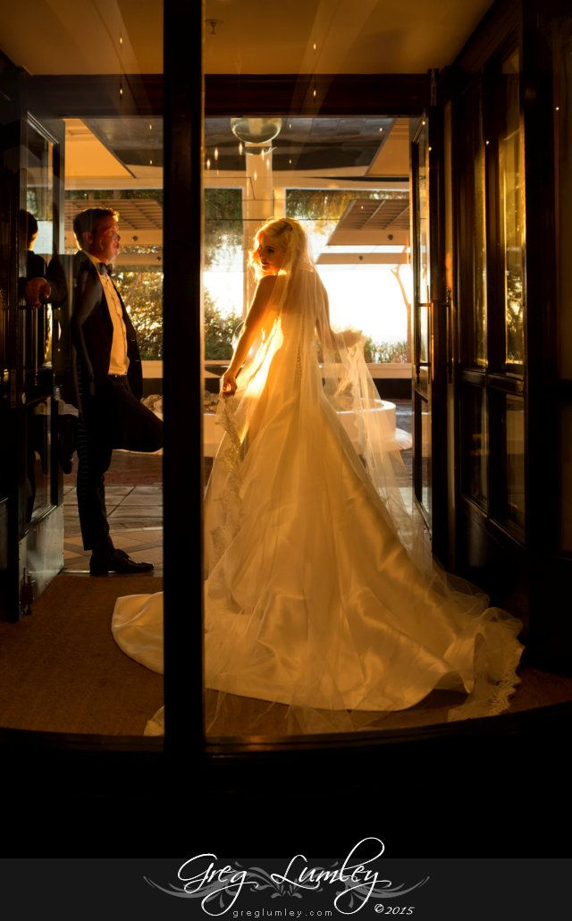 Arty picture Bride and groom stand in Twelve Apostles hotel entrance