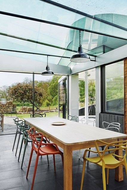 Modern glass dining area with colourful chairs. Dining room design ideas - furniture, lighting, wallpaper, dresser - by House & Garden.