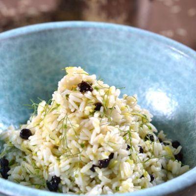 Προσθέτουμε το βούτυρο, τον χυμό, το ξύσμα του λεμονιού και τα μυρωδικά και ανακατεύουμε πολύ απαλά με μια πιρούνα, προσέχοντας να μη σπάσουμε το ρύζι και να το διατηρήσουμε σπυρωτό.