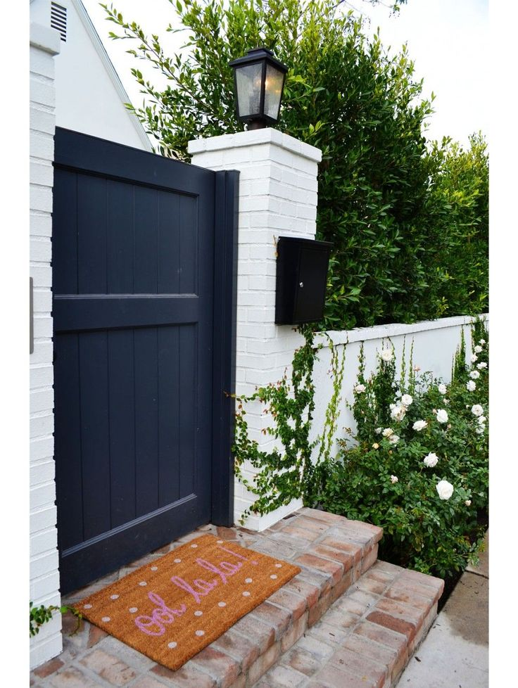 Black and white home exterior with a cute door mat
