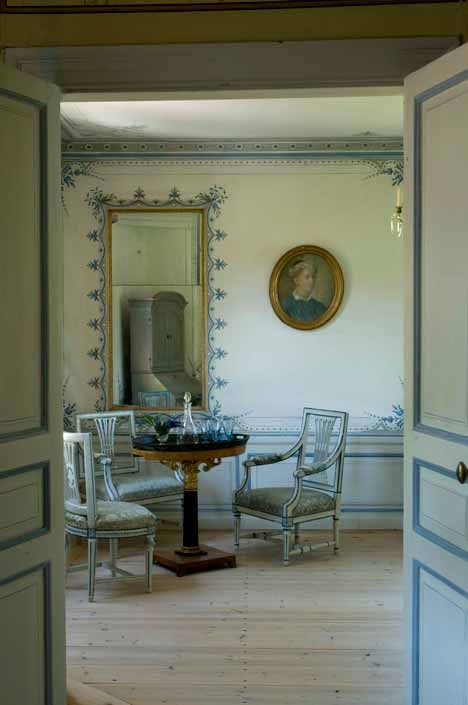 This image belongs to the Gustavian period. The colour scheme consists of light grey's and blues, with the blue being carried into the furniture. The furniture is carved and upholstered in what looks like silk.