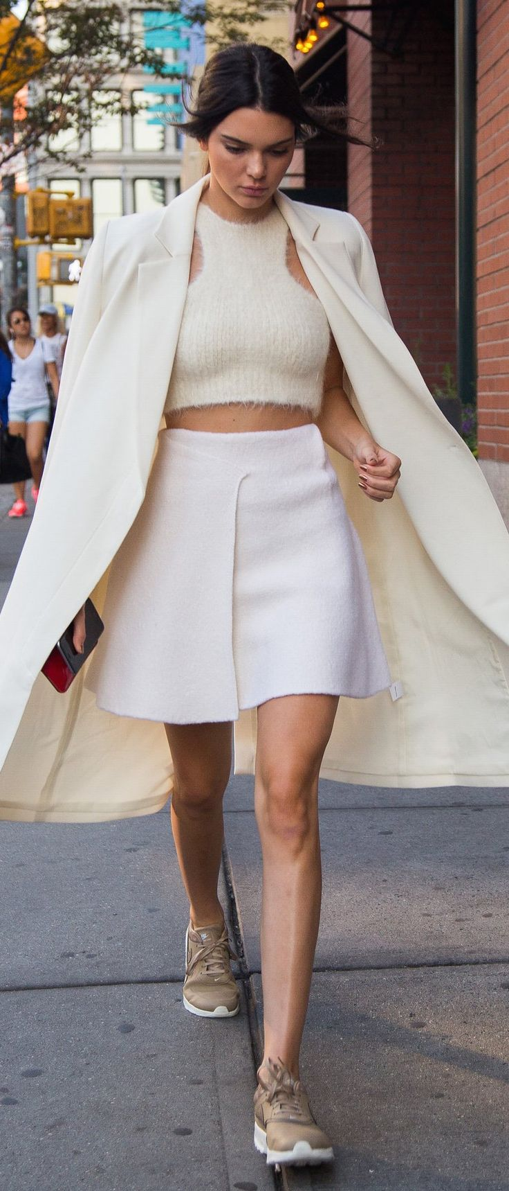 Kendall Jenner in a fuzzy crop top, a-line cream skirt, and sand-colored sneakers