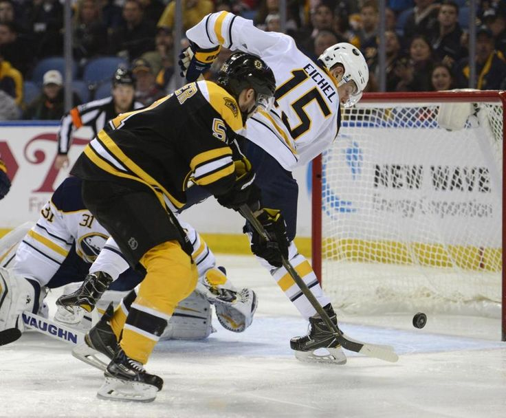 Buffalo Sabres center Jack Eichel (15) and goaltender Chad Johnson (31) defend as Boston Bruins center Ryan Spooner (51) scores during the second period of an NHL hockey game, Thursday, Feb. 4, 2016 in Buffalo, N.Y. (AP Photo/Gary Wiepert)