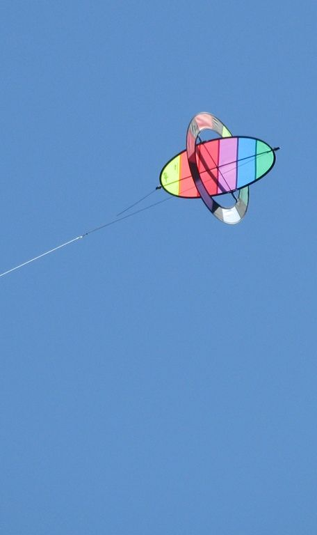 """Sticked 3D KItes. This unusual contraption is an example of a Rotor kite. The elliptical portion of this Prism Flip kite rotates rapidly on an axle, producing a lifting force. It tumbles like an airplane wing would, if detached from the aircraft! T.P. (my-best-kite.com) """"Chris's kite."""" Cropped from a photo by VanessaRyan on Flickr (cc)."""