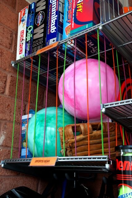 garage organization: Colorful bungee cord contains bouncy balls and sports equipment