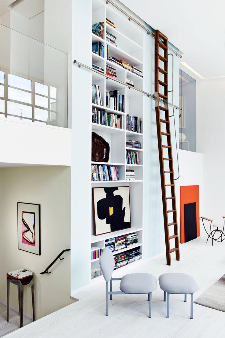 Todo el saber - AD España, © D.R. A los espacios de almacenaje se accede por una escalera de madera que se desplaza horizontalmente por unas guías metálicas. En primer plano, butaca y reposapiés de la colección Re-Imagine de Studio MAMA, a la venta en 19 Greek Street