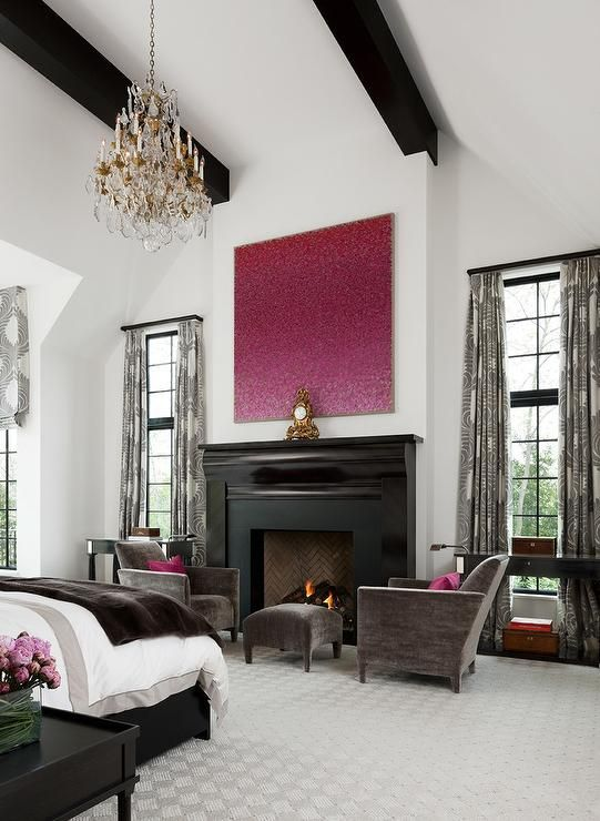 Pink and brown bedroom sitting area with a vaulted ceiling is accented with dark stained wood beams and a crystal chandelier which illuminates a pink abstract art piece above a black fireplace mantle and surround flanked by windows covered with gray print curtains lined with black demi-lune tables.
