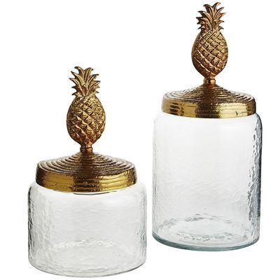 """From the Tupi word <i>nanas</i>, meaning """"excellent fruit,"""" pineapples were once considered a symbol of wealth and were often displayed at dinner parties rather than eaten. Bring home tradition with our beautiful canisters, handcrafted of hammered glass with a golden lacquered pineapple top. A wealth of style, you might say."""