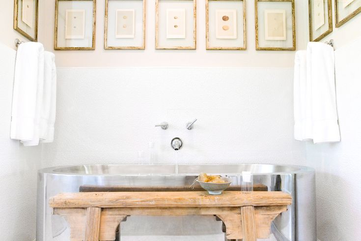 textured white bathroom walls, wooden asian bench,  silver freestanding tub, modern freestanding silver bathtub, wall mounted tub faucet, transparent picture frames w egg prints, egg art prints,