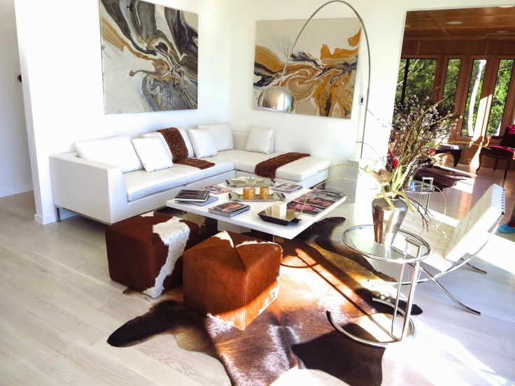 Modern Living Room With Barcelona Chair Cow Hide Animal Skin Rug And Pony Pouf Ottomans