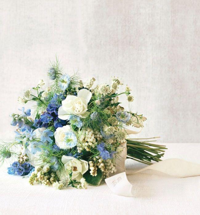 We <3 this blue + white bouquet made of nigellas, delphiniums, viburnum berries, and sweet peas