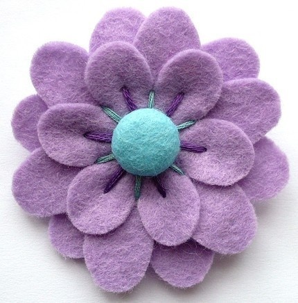 Cut out felt pieces and sew layers, choose a button to sew on to the flower shaped felt piece you just made, and you have a flower!