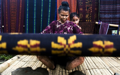 An old lady is weaving Ikat, traditionally woven fabric from Flores, East Nusa Tenggara, Indonesia.