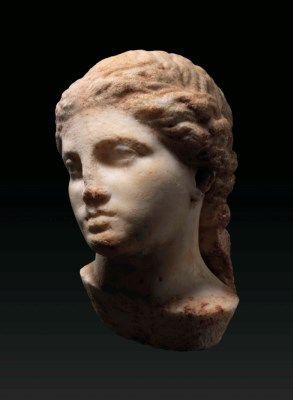 A GREEK MARBLE FEMALE HEAD  CLASSICAL PERIOD, CIRCA 4TH CENTURY B.C.