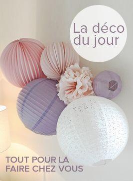 Une décoration de lampions au mur dans les tons rose et mauve