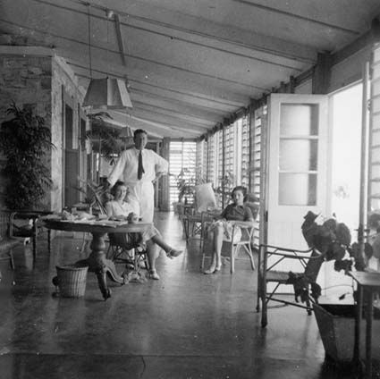 Western Verandah, Government House, Darwin in 1938 - The Administrator, Mrs Abbott, and their daughter Dorothy - In 1937, a cyclone swept through Darwin, wrecking part of the Government House and  garden. The Administrator's wife, Mrs Hilda Abbott, took on the task of refurbishing both Government House and the gardens.