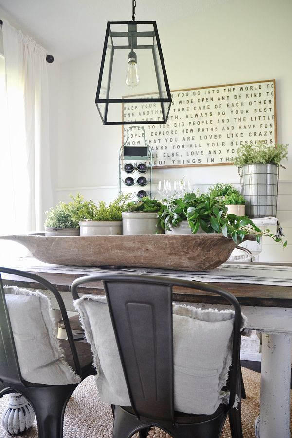 "This style is a little too ""industrial"" for me, but I do like the light fixture, the metal planter accents and all of the green plants.  I also like the natural looking woven rug."