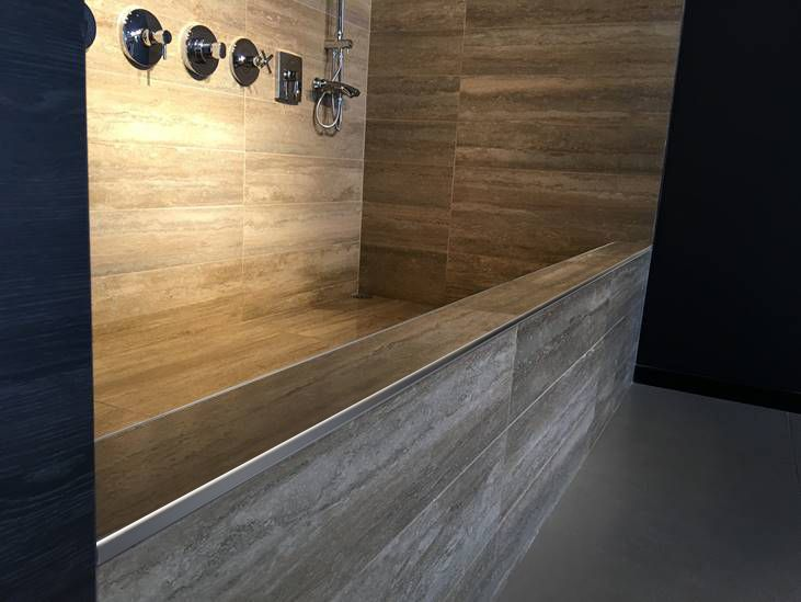 Zona de ducha revestida con madera acompa ada de varilla for Pasamanos para ducha