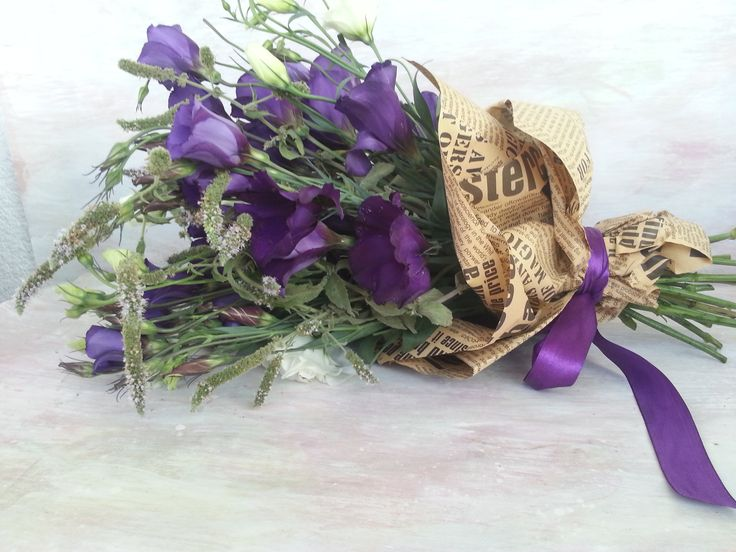 Savage bouquet with dark mauve lisianthus and newspaper wrap.