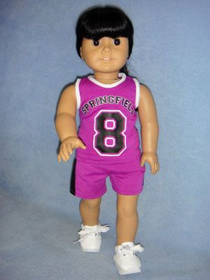 """Basketball Outfit has a purple knit tank top trimmed in white w/'Springfield 8' & Velcro fastener down the back. Matching purple knit shorts have black down the sides & elastic waist. Fits 18"""" girl dolls such as American Girl & Springfield Collection. Shown with 3"""" White Mini Sketz Shoes (67151) (not included)."""