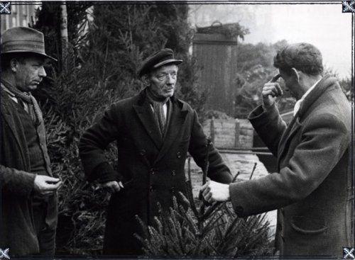 Kerstmis. Een klant van een kerstbomenverkoper wijst op zijn voorhoofd, omdat hij de verkoopprijs van een kerstboom te hoog vindt. Plaats onbekend.1932.