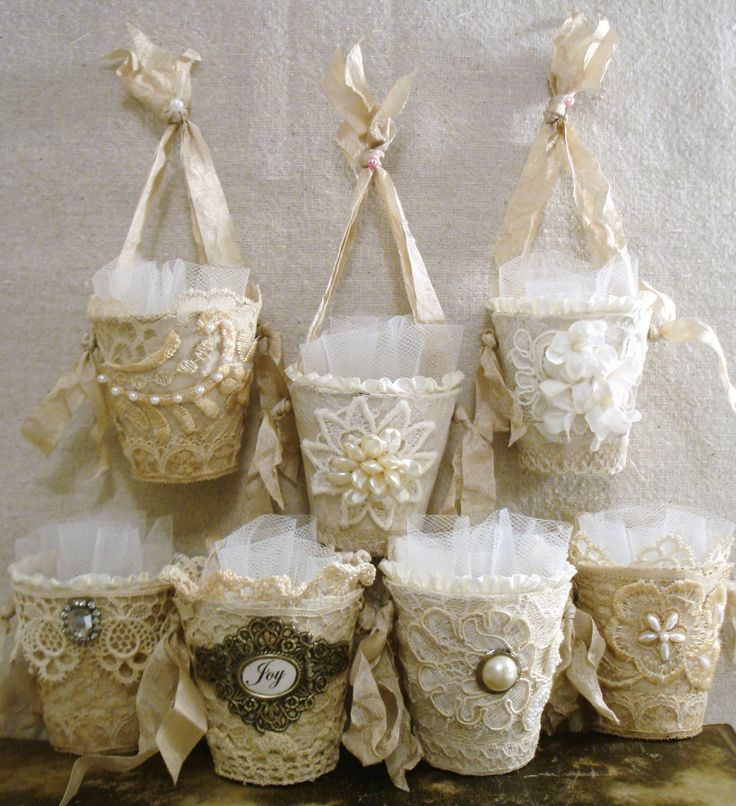 ~ The Feathered Nest ~showed these beautiful candy cups made from tiny peat pots embellished with lace, tulle and 'jewels'.  They're intended to go on the Christmas tree, but they'd be cute on a party table, too at each place setting.