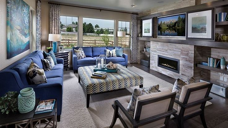 A sleek stone fireplace flanked by shelves defines this for The family room wheat ridge