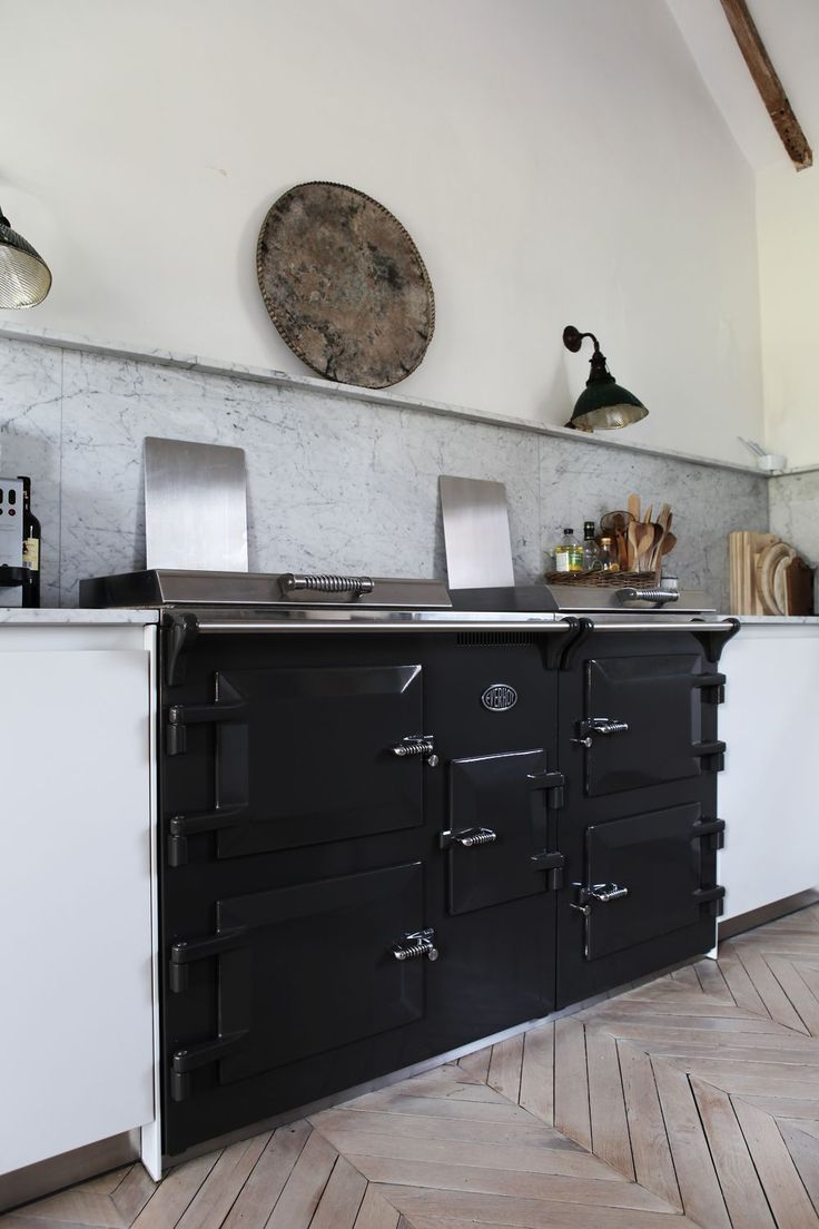 Great kitchen. Bleached wood floor, black stove, white smooth-front cupboards, small overhang of (marble?) countertop, white marble backsplash.