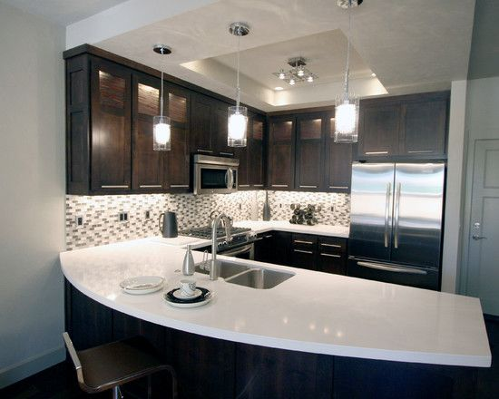 Espresso Stain Alder with quartz counters.  I love the curved peninsula, and the detail of the ceiling to enhance the lighting scheme.