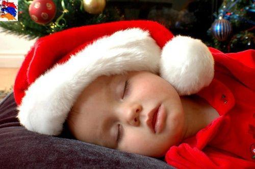 Alvó kisgyerek Mikulás-sapkában,