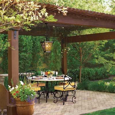 Pergola, Patio, and Chandelier. There is something cozy about the low hedges on the sides of the pergola.