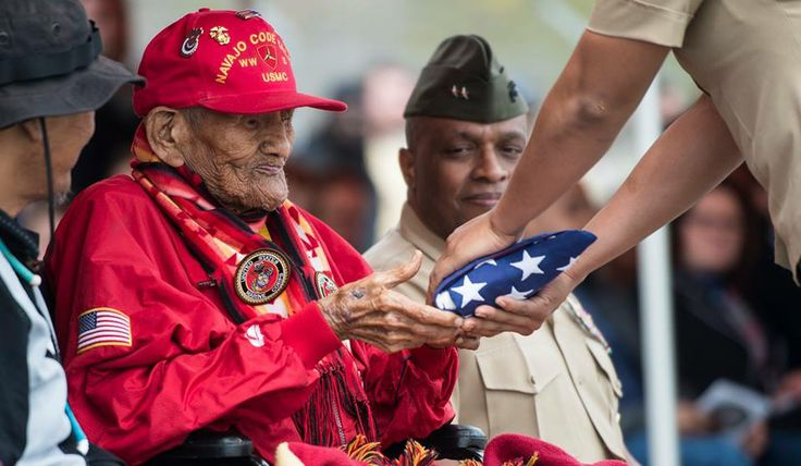 U.S. Marine Corps Cpl. Chester Nez receives an American flag from Pfc. Tiffany Boyd, at Code Talker Hall, Marine Corps Base Quantico, Va., April 4, 2014. The flag was flown over the Marine Corps War Memorial, on the first day of spring in honor of Cpl. Nez's attendance at the Platoon 382 Hall rededication. Cpl. Nez is the last of the original 29 Navajo Code Talkers of World War II. (U.S. Marine Corps photo by Cpl. Kathryn K. Bynum/Released) http://dvidshub.net/r/86h5cn