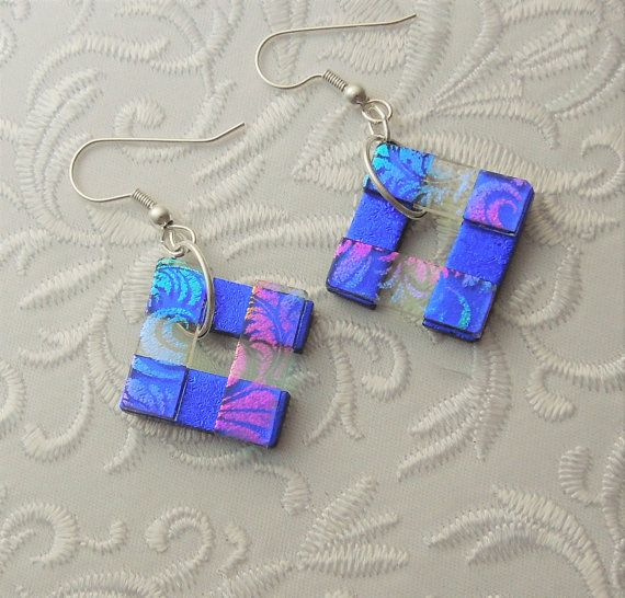 These dichroic glass earrings are stacked and lightly fused to maintain a crisp dimensional square shape. Main colors are blue and pink with hues of yellow dichroic glass. Super cute earrings! Very Light weight. Just about 3/4. Sterling silver ear wires. Here are some of my other glass earrings >>> https://www.etsy.com/shop/GalaxyGlassStudio?section_id=5903483&ref=shopsection_leftnav_1  Enter my shop here: galaxyglassstudio.etsy.com Sign up for my newsletter for special coupons and monthly…