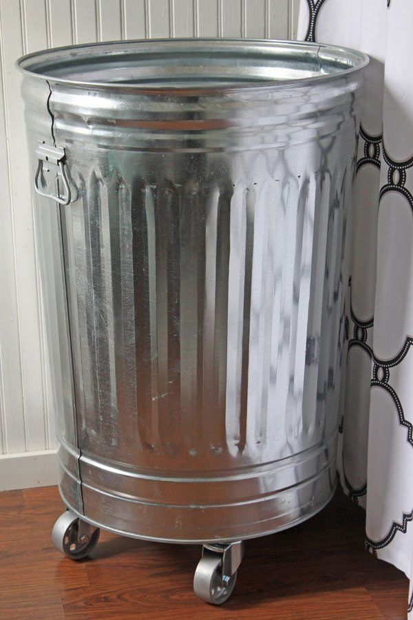 a couple smaller metal trash cans on wheels under the craft table