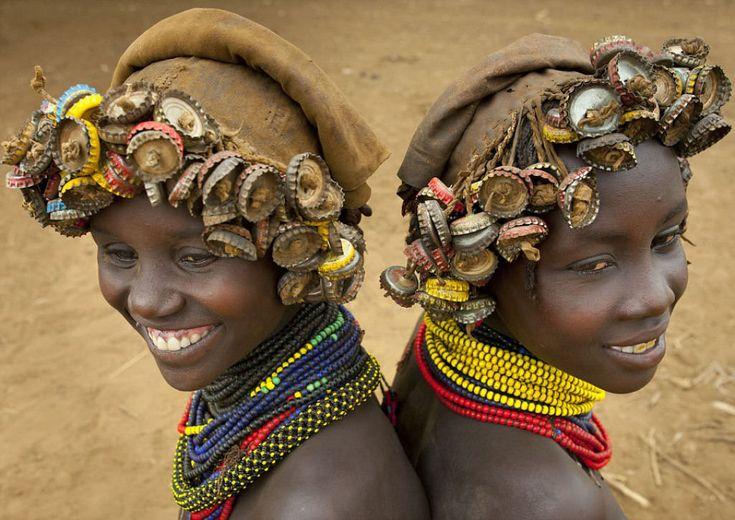 """O incrível """"mundo fashion"""" espremido entre uma tribo da Etiópia e os centros urbanos. Veja como o descarte urbano que chega pelo Rio Omo vira perucas de tampinhas e brincos feitos de pedaços de relógios quebrados."""
