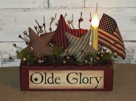 MADE TO ORDER~SHIPPING TIME CAN BE UP TO 2 WEEKS #sum 101 Primitive Olde Glory Americana Homespun Star Arrangement I have painted this Olde Glory box in barn red with black underneath the topcoat. I have added three of my hand made Americana homespun stars with accents of primitive berries and a electric light. American flag may be out of the arrangement for shipping purposes. Lighting is optional with this item. You can get it without any lighting, or add a grungy battery taper, grungy…