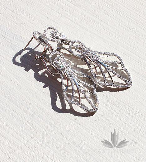 Klasyczne kolczyki wiszące w kształcie ażurowych ornamentów, wykonane ze srebra próby 925, rodowane. Wyrób wysadzany cyrkoniami o szlifie brylantowym. Bardzo wygodne zapięcie dociskowe, klips. Przepięknie wykończone, fantastycznie nadają się jako uzupełnienie sukni ślubnej lub wieczorowej. Całkowita długość wzoru to około 5,0 cm.