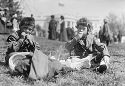 Two children enjoy treats during the annual Easter egg roll at the White House lawn on Easter Monday, 1911