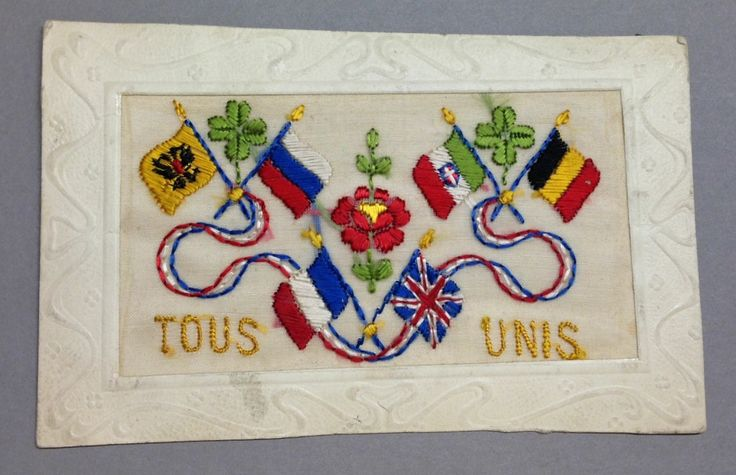 """WW1 World War One Silk Postcard from the Toronto Public Library collection """"Tous Unis"""" all united - circa 1915 / 1916.  Showing flags of allied nations Britain & France (centre) ,  Italy & Belgium (on the right)  and (on the left) Imperial Russia and either  Russia again or possibly Serbia was intended - but the colors inverted - should have been red/blue with white on bottom."""