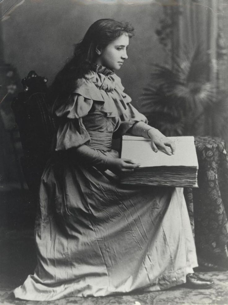 Circa 1889 black and white portrait of Helen Keller as an adolescent reading a large embossed book that is resting in her lap.