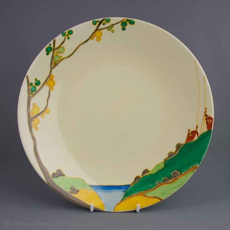 This is a Clarice Cliff Bizarre Secrets pattern plate Decorated in Secrets pattern Hand painted with a stylised tree and a cottage landscape This