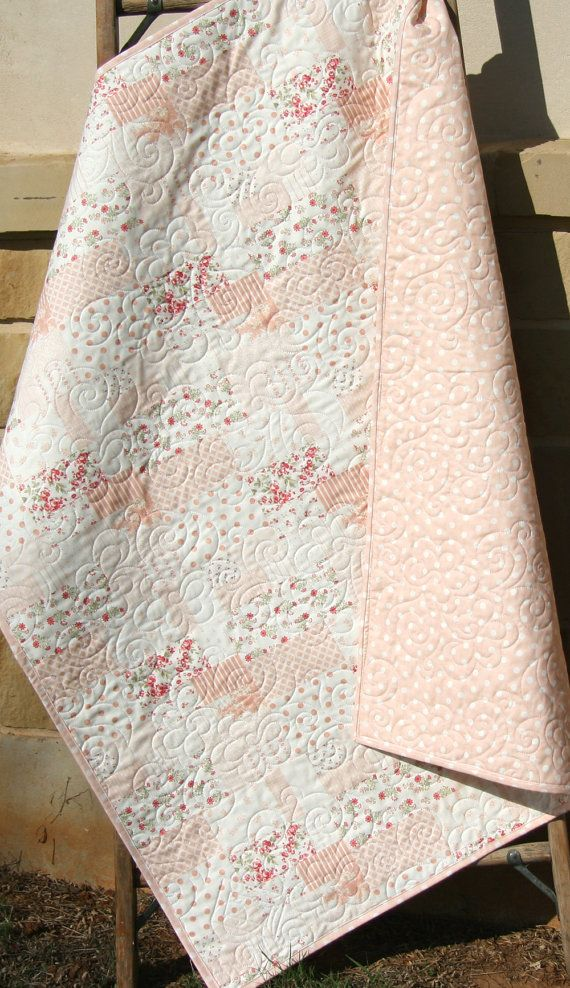 This beautiful quilt was made with the Whitewashed by 3 Sisters for Moda Fabrics. This adorable quilt includes subtle shades coral pink, white and hints of red. You can choose the size baby (37x44) or toddler (37x53). The backing is a coordinating print which features coral pink dots. This is a whoelcloth quilt in which the pattern is printed directly on the fabric. The quilting really adds to the beauty of this quilt! A quilt is three layers stitched together, with the middle layer being a…