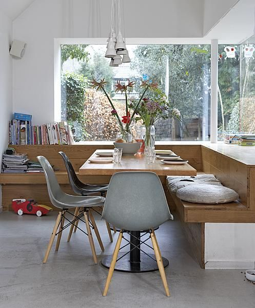 Dining area: simple fixed wooden seating with cushions above for comfort. Slide out storage below. Provides 'shelf' by windows for nic nacs.
