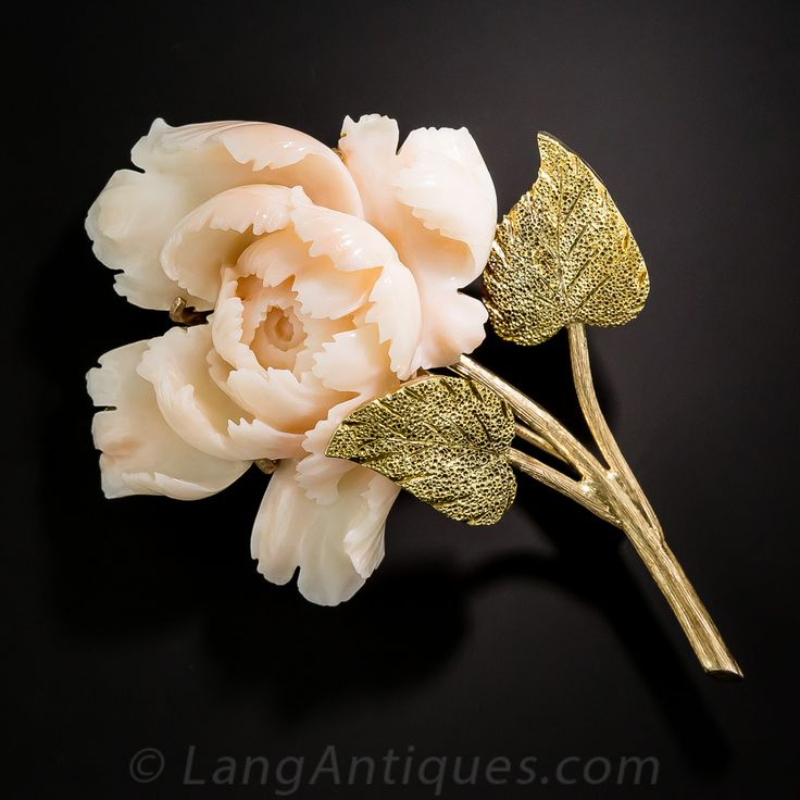 Long regarded as an omen of good fortune and happy marriage, this precious peony brooch, circa 1940s-50s, is lovingly rendered in hand carved angel skin coral with realistically textured 14K gold stem and leaves that beautifully support the deckle-edged, wispy folds of the lush, full bloom. 2 3/4 by 1 7/8 inches. Beautiful!