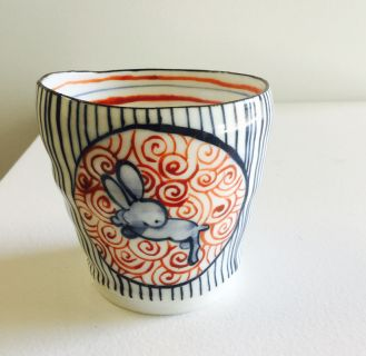 Red and blue glazed porcelain tumbler with Japanese influenced illustration.